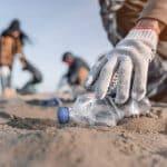 personne ramassant une bouteille en plastique sur la plage
